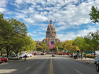 The view from Congress Avenue from all the way to south Austin leads straight to an unobstructed view of the Texas State Capitol. On this day the US flag hoisted by cranes on the Austin Fire Department Fire trucks.