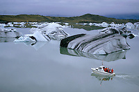 Tourist boat navigating through floating icebergs in the waters of Jokulsarlon, the largest glacier lake in Iceland.