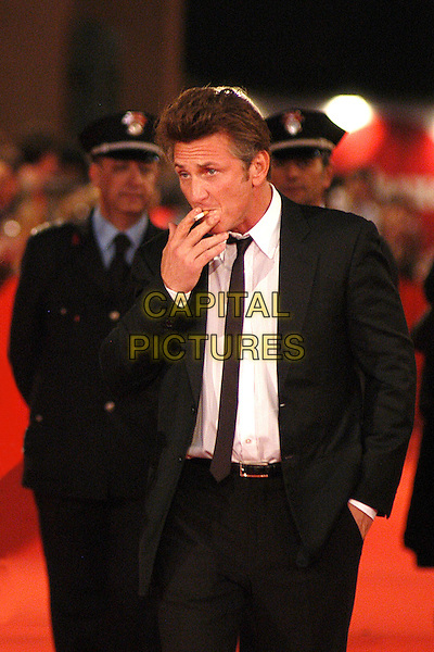 """SEAN PENN .Red carpet arrivals for the film """"Into The Wild"""" during the 2nd Annual Rome Film Festival, Rome, Italy..Red carpet arrivals for the film """"Into The Wild"""" .October 24th, 2007.half length black suit jacket smoking cigarette hand in pocket.CAP/CAV.©Luca Cavallari/Capital Pictures."""