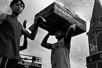 A Brazilian dock worker carries a large wooden box full of fish on his head in the port of Belem, Brazil, 2 March 2004. Amazonia is the world's largest dense tropical forest area. Since the 16th century the original indigenous people have been virtually pushed away or exterminated. The primal ancient unity between tribes and the jungle ambient has changed into a fight between the urban based civilization and the jungle enviroment. Although new generations of white and mestizo settlers have not become adapted to the wild tropical climate and rough conditions, they keep moving deeper into the virgin forest. The technological expansion causes that Amazonia is changing rapidly.