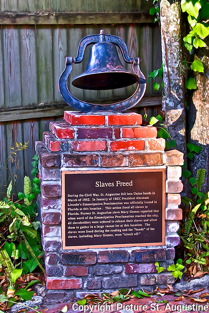 """A Bell on top of a marker commemorating """"Slaves Freed"""". Former St. Augustine slave Mary Gomez reported in an early 20th century St. Augustine newspaper article that when word of the Emancipation Proclamation reached the city, all slaveholders were ordered to release their slaves and allow them to gather in a large vacant lot at the location where the proclamation was to be read. The slaves were freed during the reading and the ''bonds'' of the slaves, including Mary Gomez, were ''struck off.''"""