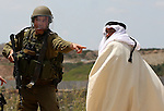 An Israeli soldier scuffles with A Palestinian man during the weekly demonstration against Israel's controversial separation barrier in the village of Bilin, near the West Bank city of Ramallah on April 22, 2011. Some 250 left-wing Israeli and foreign activists protested in the West Bank village of Bilin against the separation fence being built in the area. Some of the protestors hurled stones at the security forces, who used crowd dispersal means in response. Photo by Issam Rimawi