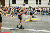 Switzerland. Canton of Neuchâtel. Neuchâtel. Grape Harvest Festival. During the parade (corso), a group of young boys with roller skates are pulled by ropes behind a cart. They are wearing wetsuits, helmets, floating jackets and waterskis on their feet. © 2006 Didier Ruef