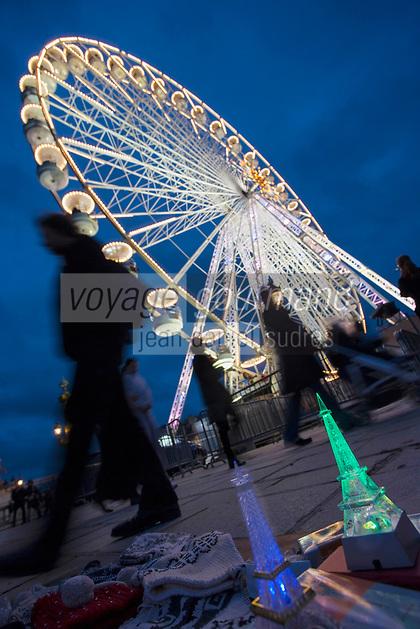 Europe/France/Ile-de-France/75001/Paris:   Tour Eiffel souvenir miniature  sur l'étal d'un marchand à la sauvette et  Grande roue, Place de la Concorde  // Europe / France / Ile-de-France / 75001 / Paris: Miniature souvenir Eiffel Tower on the stall of a street vendor and Ferris wheel, Place de la Concorde