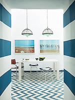 A striking blue and white dining room with a zig zag pattern floor. The room features a table by Habitat and vintage chairs by Harry Bertoia and Mart Stam.