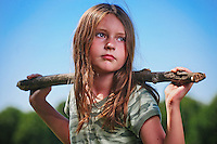 Young girl wearing camouflage tshirt carries large stick from woods with blue sky background