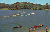 """Bella Vista Historical Museum<br /> Lake Bella Vista used to be larger than it is today. This picture was taken in the 1950's, when E. L. Keith, standing in the lower right corner, was the owner. His motel and restaurant are shown in the background, at the west end of the Lake Bella Vista dam. The postcard was still available in the 1960's, and this one is postmarked August 17, 1966, by which time Cooper Communities owned the Lake Bella Resort and used the former Sunset Hotel up on the mountain, renamed Village Hall, for visitors to check in for with a sales rep, who would take them out for a tour and try to convince them to buy a lot. This postcard was sent to the Wylies in Oklahoma City. The message reads, """"The white house on mt. is where we checked in. We have a 3 bedroom, kitchen, living room and dining table in a brand new cottage. Air cond. to boot. It's beautiful here, am trying to get pictures. Love, Benna."""""""