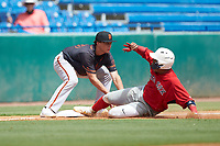 Chris Moore (32) of Suffield Academy in Brooklyn, NY playing for the Boston Red Sox scout team is tagged out at third base by Gavin Conticello (83) of Coral Springs Charter in Coconut Creek, FL playing for the San Francisco Giants scout team during the East Coast Pro Showcase at the Hoover Met Complex on August 3, 2020 in Hoover, AL. (Brian Westerholt/Four Seam Images)