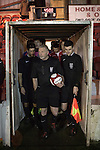 Ashton United 6 Ramsbottom United 0, 12/01/2016. Hurst Cross stadium, Northern Premier League. The referee and his assistants waiting to take the field before the fixture between Ashton United and Ramsbottom United in the Northern Premier League premier division. The match was played at Ashton's Hurst Cross stadium, the club's ground. The club was originally founded in 1878 as Hurst F.C. and by 1880 the club were playing at Hurst Cross, their current ground which makes their home one of the oldest football grounds in the world. Ashton won the match 6-0, watched by a crowd of 178. Photo by Colin McPherson.