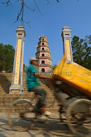 Asia, Vietnam, Hue. Tricycle passing the Thap Phuoc Duyen (Source of Happiness Tower) at Thien Mu (Heavenly Lady Pagoda). Designated a UNESCO World Heritage Site in 1993, Hue is honoured for its complex of historic monuments. Overlooking the river Huong (Perfume River) and set amidst verdant greenery, the Thien Mu Pagoda is the oldest pagoda in Hue. Built in 1601 the 21meter high seven-story octogonal tower Thap Phuoc Duyen is now the official symbol of the city Hue.