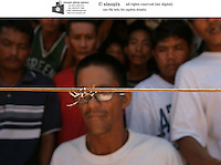 PEK0 20030914 BACOLOD, PHILIPPINES : Local residents watch and wager on spider fights in a slum area in Bacolod, Philippines on Sunday, 14 September, 2003. The spiders are found in the fields, and then are matched up for fights against each other. The spider fighting season lasts about three months every year.