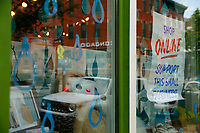 """""""Shop Online Support This Small Business"""" signs hang on businesses throughout the Lawrneceville neighborhood on Saturday April 18, 2020 in Pittsburgh, Pennsylvania. (Photo by Jared Wickerham/Pittsburgh City Paper)"""