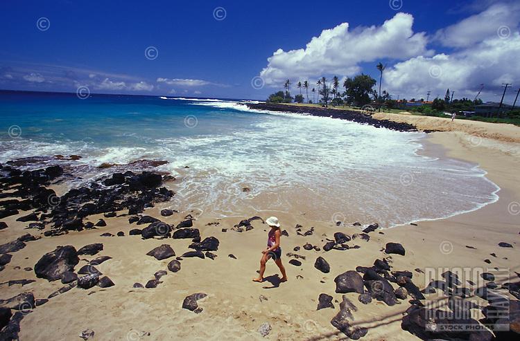 Woman on beach surrounded by blue Pacific Ocean at Poipu Beach, Kauai, Hawaii