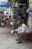 Man reading newspaper in Ho Chi Minh City - District One, June 2017