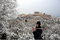 Pictured: A tourist takes a picture of the snow covered ancient monument of the Acropolis, Athens, Greece. Tuesday 10 January 2017<br /> Re: Heavy snow fall and minus zero temperatures have affected most parts of eastern Europe and Greece.