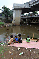 Indonesian children sit next to a polluted river in central Jakarta.<br /> <br /> To license this image, please contact the National Geographic Creative Collection:<br /> <br /> Image ID: 1588058 <br />  <br /> Email: natgeocreative@ngs.org<br /> <br /> Telephone: 202 857 7537 / Toll Free 800 434 2244<br /> <br /> National Geographic Creative<br /> 1145 17th St NW, Washington DC 20036
