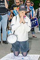 """A woman wearing a Trump campaign hat kneels in prayer as people gather for an anti-lockdown protest organized by the alt-right group Super Happy Fun America near the home of Massachusetts governor Charlie Baker in Swampscott, Massachusetts, on Sat., May 16, 2020. The protest was in defiance of Massachusetts orders mandating face coverings and social distancing and prohibiting gatherings larger than 10 people during the ongoing Coronavirus (COVID-19) global pandemic. The state's stay-at-home order is expected to be updated on May 18, 2020, with a phased reopening plan issued by the governor as COVID-19 cases continue to decrease. Anti-lockdown protests such as this have become a conservative cause and have been celebrated by US president Donald Trump. Many of the protestors displayed pro-Trump messages or wore Trump campaign hats and shirts with phrases including """"Trump 2020"""" and """"Keep America Great."""" Super Happy Fun America, organizers of the protest, are an alt-right organization best known for creating the 2019 Boston Straight Pride Parade."""