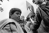 State of Palestine. West Bank. Balata Camp. Palestinian refugees. Young men and boys hold a peace demonstration before the opening in Madrid of first round of talks between Israel and the Arab World. The Madrid Conference was a peace conference, held from 30 October to 1 November 1991 in Madrid. It was an attempt by the international community to revive the Israeli–Palestinian peace process through negotiations, involving Israel and the Palestinians as well as Arab countries. Balata Camp is a Palestinian refugee camp established in the northern West Bank in 1950, adjacent to the city of Nablus. It is the largest refugee camp in the West Bank. Balata Camp is densely populated with 30,000 residents in an area of 0.25 square kilometers. In 1991, Balata Camp was living under Isreal's occupation and rules as part as the Occuppied Territories. In the 1980s and 1990s, Balata residents played a leading role in the uprisings known as the First Intifada and the Second Intifada. Balata Camp is since 1993 under palestinian authority, located in the A zone. The Palestinian National Authority (PA or PNA) was the interim self-government body established to govern Areas A and B of the West Bank as a consequence of the 1993 Oslo Accords. Following elections in 2006, its authority had extended only in areas A and B of the West Bank. Since January 2013, the Fatah-controlled Palestinian Authority uses the name State of Palestine on official documents. The Palestinian keffiyeh is a gender-neutral chequered black and white scarf that is usually worn around the neck or head. The Palestinian keffiyeh has become a symbol of Palestinian nationalism. The Palestinian flag is based on the Flag of the Arab Revolt, and is used to represent the Palestinian people. © 1991 Didier Ruef