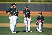 (L-R) Will Craig (22), Johnny Aiello (2), Nate Mondou (10), and Gavin Sheets (24) of the Wake Forest Demon Deacons wait for the new pitcher to complete his warm-ups during the game against the Florida State Seminoles at David F. Couch Ballpark on April 16, 2016 in Winston-Salem, North Carolina.  The Seminoles defeated the Demon Deacons 13-8.  (Brian Westerholt/Four Seam Images)
