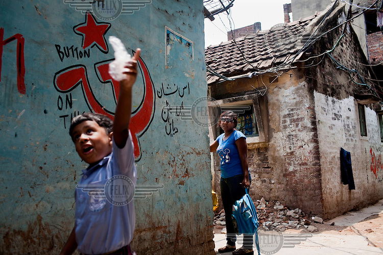 Razia Shabnam (in blue) reaches her home after walking with her son, Saihaan, through the alleyways of Ekbalpore. A hammer and sickle graffiti adorns a wall beside them. 28 year old Razia Shabnam was one of the first women boxers in Kolkata and also the first woman in her community to go to college. She is now a coach and one of only three international female boxing referees in India.