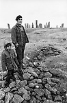 Villagers father and son at Callanish Standing Stones.They are standing on a pile of stones from an excavated burial cyst.  Isle of Lewis and Harris,  Outer Hebrides, Highland and Islands Scotland 1974