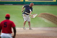 LSU grounds crew member spreads quick-dry during a rainstorm at the NCAA Super Regional baseball game against Stony Brook on June 9, 2012 at Alex Box Stadium in Baton Rouge, Louisiana. Stony Brook defeated LSU 3-1. (Andrew Woolley/Four Seam Images)