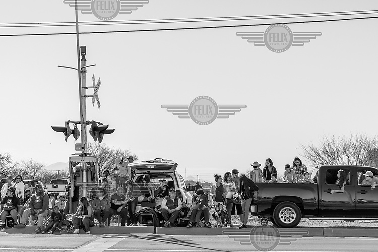 Spectators line the street at a rodeo parade.