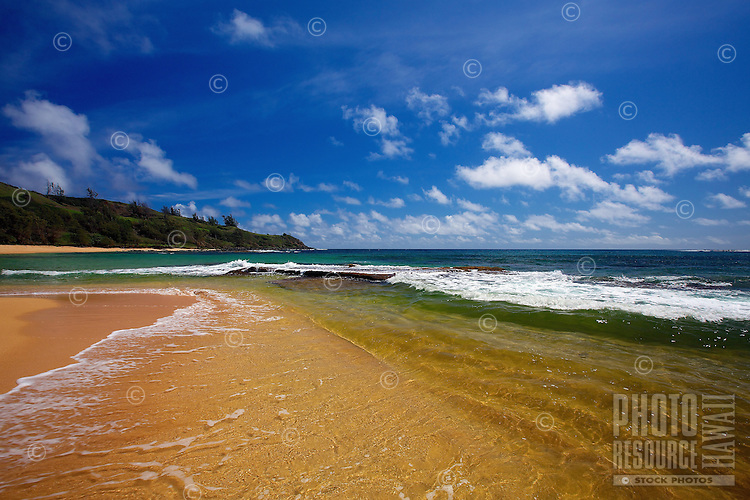 A perfect day at Moloa'a Bay and Beach, with clear skies and a see-through ocean wave breaking gently onto the golden sand, northeastern Kaua'i.