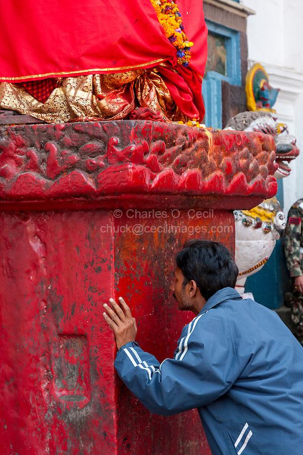Nepal, Kathmandu.  Young Man Worshiping at Hanuman Statue, Durbar Square.