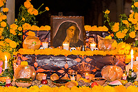 Oaxaca, Mexico, North America.  Day of the Dead Celebrations.  Family Altar Decorations in Memory of the Dead, San Miguel Cemetery.  Skull, Flowers, Marigolds, bread of the Dead (Pan de Muertos), candle.