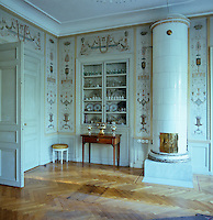 A collection of porcelain and glassware is displayed in this room which features hand-painted Pompeian style panels and a large tiled stove