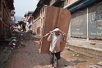 A man carries on his back a wardrobe recovered from the rubble. Shanku, near Kathmandu, Nepal. May 9, 2015