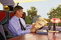 Man reading newspaper, with laptop computer, travelling on train. Model released.