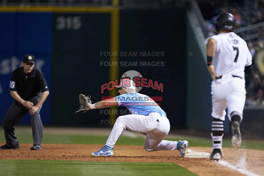 Jacob Olson (7) of the South Carolina Gamecocks hustles down the first base line as Michael Busch (15) of the North Carolina Tar Heels waits for a throw at BB&T BallPark on April 3, 2018 in Charlotte, North Carolina. The Tar Heels defeated the Gamecocks 11-3. (Brian Westerholt/Four Seam Images)