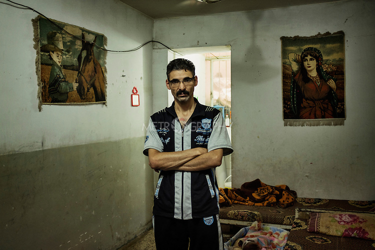 """29/08/15. Shaqlawa, Iraq. -- Imad, 38 y.o. from Falluja lives in a 12 square meters room in a basement of a disused building at the centre of the bazar, and for which he pays 300.00 IQD (250usd) per month. A former employee of the ministry of industry in Falluja, Imad lives with his wife and two children. He says """"we don't complain about the rats and mice: we live with them, we got used. But the snakes, those are dangerous, they are silent, and they bite."""""""
