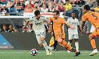 FOXBOROUGH, MA - JUNE 29: Carles Gil #22 dribbles as Tommy McNamara #11 pressures during a game between Houston Dynamo and New England Revolution at Gillette Stadium on June 29, 2019 in Foxborough, Massachusetts.