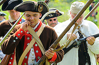 Continental Army soldier bites the end off a powder cartridge as he reloads his flintlock musket during a Revolutionary War re-enactment at Fort Ticonderoga, New York, USA.