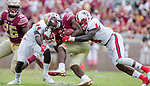 North Carolina State defenders Shawn Boon (24) and Jerod Fernandez (4) bring down Florida State running back Cam Akers in the second half of an NCAA college football game in Tallahassee, Fla., Saturday, Sept. 23, 2017.  NC State defeated Florida State 27-21. (AP Photo/Mark Wallheiser)