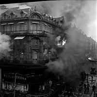 """Edifice commercial et de bureaux, magasin """"Au gaspillage"""" au début du XXe siècle, """"Au bon marché de Paris, """"le Printemps"""" et les assurances """"Le continent"""" dans les années 1960, """"Bouchara"""", """"Zara"""", 47 rue d'Alsace-Lorraine.. 11 Mars 1964. Vue de l'incendie de l'immeuble du Printemps et de l'intervention des pompiers : vue prise en hauteur d'un immeuble en face ; l'immeuble ravagé par le feu, entouré de nuages de fumée épaisse, des lances à incendie, la grande échelle au second plan ; des flammes sortent des fenêtres du troisième étage."""