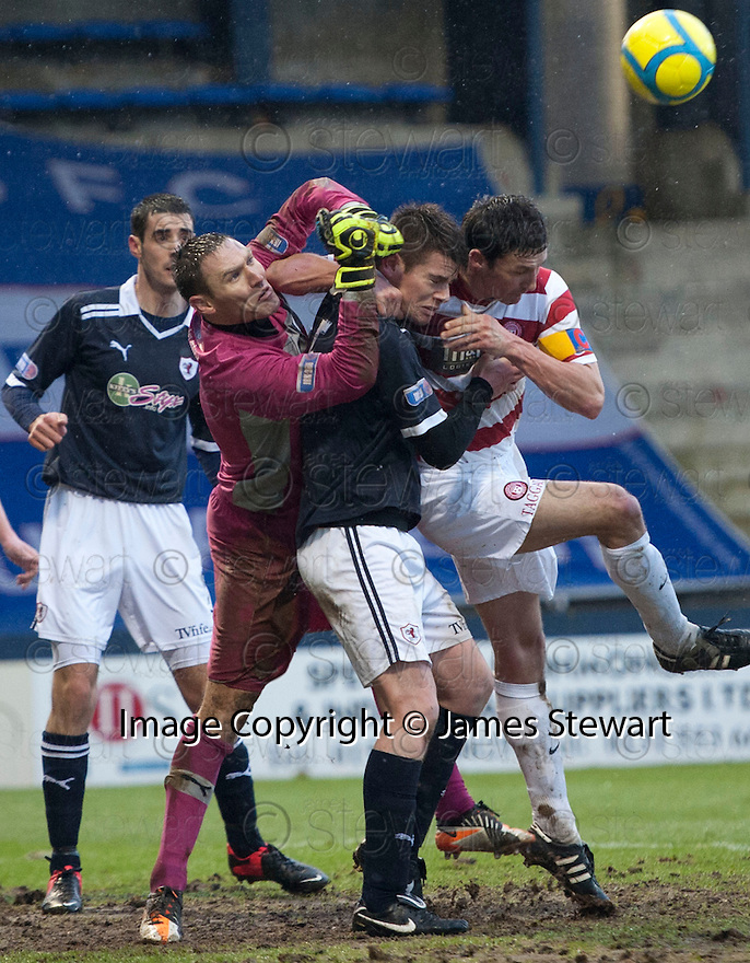 Raith goalkeeper David McGurn punches clear as Dougie Hill holds off Accies Martin Canning.