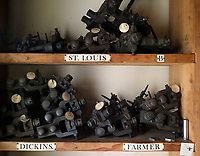 Machine parts for different fonts are stored on labelled shelves