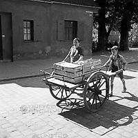 Eine Marktfrau und ihr Sohn schieben einen Handkarren durch die Straßen von Augsburg, Deutschland 1930er Jahre. A market woman and her son pushing a cart through the streets of Augsburg, Germany 1930s.