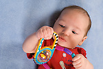 3 month old baby boy holding toy rattle in fist palmar grasp closeup on back