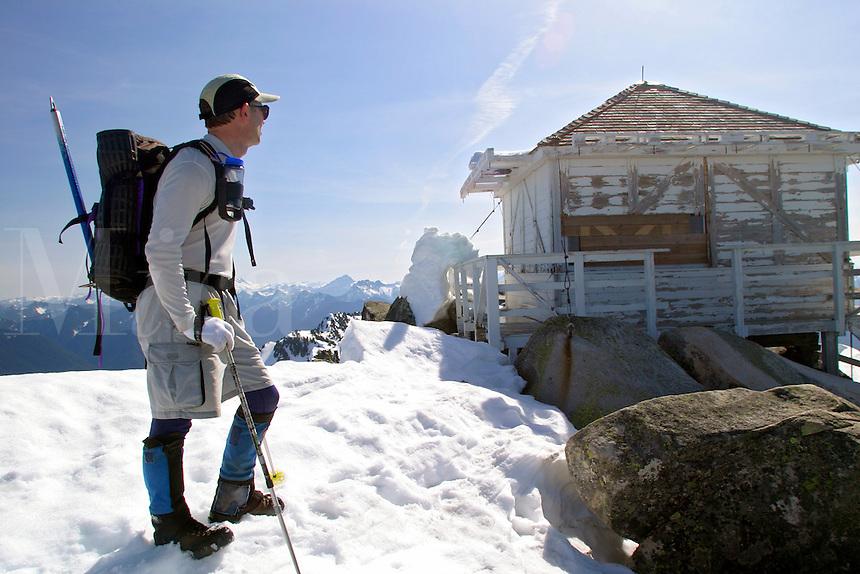 Man walking on snow towards Mount Pilchuck Lookout, Snohomish County, Cascade Mountains, Washington, USA