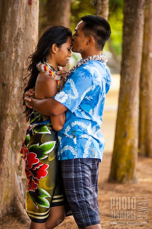 A young local man kisses his fiancée under the trees at Kailua Beach Park, Windward O'ahu.
