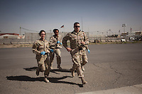 US Navy corpsmen run to a US Army medevac helicopter to transfer a wounded patient into the hospital at Kandahar airfield.