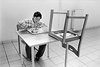Hungary. Baranya County. Pécs. Gandhi High School. A boy enjoys his lunch in the school cafeteria. He is seated alone at a table. A chair is placed upside down on the table. The purpose of the middle school / high school is to provide a school-leaving exam (A-level), also to improve the prospects of Romani children in Hungary and to help preserving the Romani culture. The Romani people, also known as the Roma, are an Indo-Aryan people group, traditionally nomadic itinerants living mostly in Europe. The Romani people are widely known in English by the exonym Gypsies (or Gipsies), which is considered by many Romani people to be pejorative due to its connotations of illegality and irregularity as well as its historical use as a racial slur. In many other languages, they are called Roms (Rroms), Tziganes,Tsiganes, Gitans, Bohémiens, Manouches, Romanichels, gitano, zingaro and cigano. The Gandhi High School in Pécs, was founded with donations given by several individuals from the private sector mostly those of Romani origin Romani and with further donations from other organizations. In 1992, the Gandhi High School became  the first Romani high school, that has been actively operating since 1994. It was named after the Indian Mahatma Gandhi, to emphasize the Indian origin of all Romani groups. The school consists of 6 classrooms where about 250 male and female pupils study, mostly between the ages of 14 to 18. The first group of students beginning in 1994 took their school-leaving exam (A-level) in 2000 and out of 18 pupils, 16 have applied to universities, while 7 out of the 18 students gained entry to their desired universities. Pécs is the fifth largest city of Hungary. It is the administrative and economic centre of Baranya County. 11.05.95  © 1995 Didier Ruef