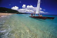 Group of people sailing a catamaran in clear blue waters off white sand beach of Waimea Bay, North Shore of Oahu, Hawaii