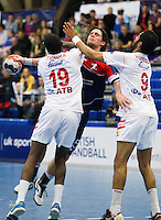 06 APR 2012 - LONDON, GBR - Great Britain's Martin Hare (GBR)  (centre, #15, in blue and red) finds his path to goal blocked by Tunisia's Mosbah Sanai (TUN) (left) and Tunisia's Oussama Hosni (TUN) (right)  during the men's 2012 London Cup match at the National Sports Centre in Crystal Palace, Great Britain .(PHOTO (C) 2012 NIGEL FARROW)