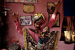 Santosh Bhaat, a puppeteer posing with his puppet in his house at Katputly colony. Dubai, Holland, Spain, France, Germany and Belgium are the countries where he performed. New Delhi, India. 15.11.2009. Kathputly colony is a slum area in West Delhi. This slum seems like any other slum areas of modern India with dysfunctional electricity, non existing sanitation and poverty. As a part of Delhi, this is also ailed with water crisis. Large families live their lives crammed together in a single room with all the odds which complement poverty. One thing which differentiates this slum with any other is the people living in the colony. Nearly everybody in this slum is a traditional performing artist; and they have been migrating to this area for last 50 years from different parts of the country for a better livelihood. They are magicians, acrobats, jugglers, puppeteers, dancers and musicians. These artistes perform in star rated hotels, marriage ceremonies of the richer section, functions, and festivities all around the country and the world. Most of the artisans I met here, have performed in Europe and America but such opportunities are rare to come by. They struggle to keep their art form alive. They say that they don't get any help or support from the government for their basic needs and for the well being of the Kathputly colony -  though they have uphold the prestige of the country internationally. Polluted air, dirty alleys smelling of urine, colourful dress and sound of music characterise Kathputly colony, which is the one of its kind in India. Arindam Mukherjee